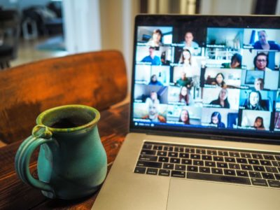 mug next to computer showing Zoom meeting